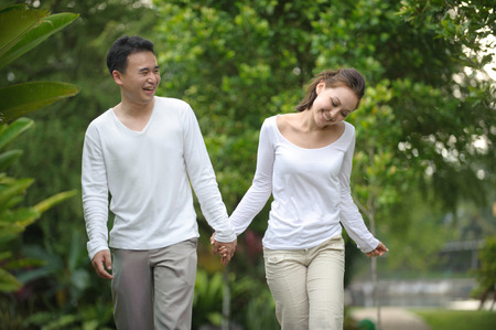 strolling: Asian couples walking in the park together enjoying each other Stock Photo