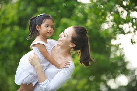 Asian mum and daughter enjoying each others company in the park Stock Photo