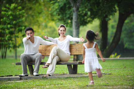 disfrutar: Familia asi�tica feliz disfrutando de su tiempo en el parque