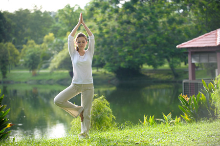 Attractive Healthy Asian Woman doing yoga in the park photo