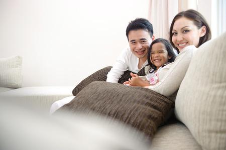 Familie lacht graag in de woonkamer Stockfoto