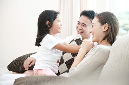 familia: Familia asi�tica feliz que juega con la hija en la sala de estar