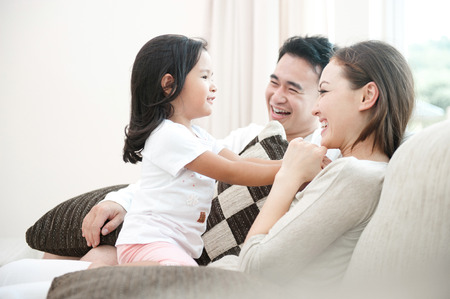 family on couch: Happy Asian Family Playing with daughter in the living room
