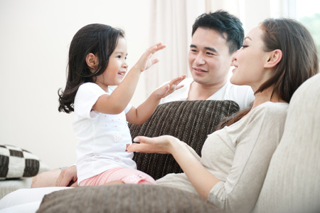 family sofa: Happy Asian Family Playing with daughter in the living room