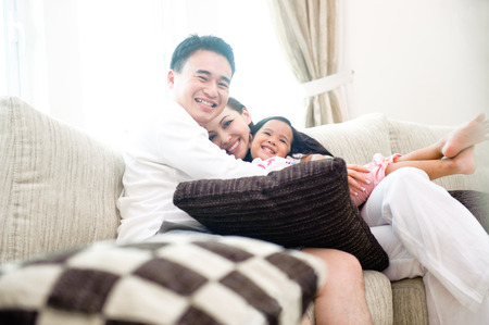 Happy Asian Family Sitting in the sofa happy with each other photo