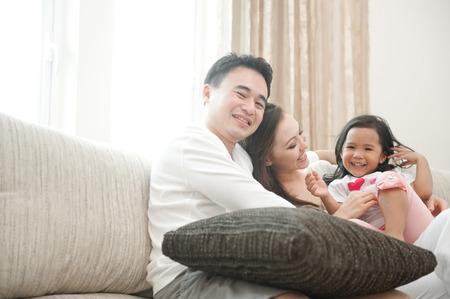 Happy Asian Family enjoying time together sitting on sofa photo