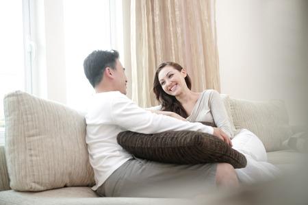 happy asian couple: Happy asian couple sitting on the sofa enjoying each others company