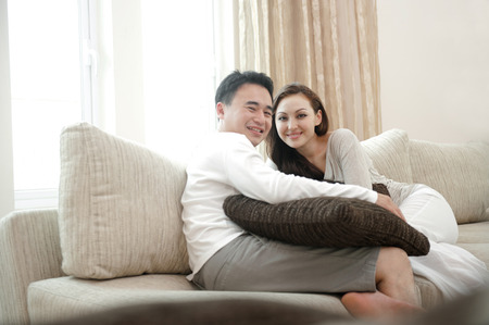Happy asian couple sitting on the sofa enjoying each others company photo