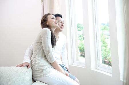 descansando: Pareja asi�tica feliz que se sienta junto a la ventana sonriendo y disfrutando