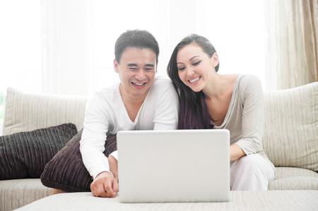 Happy Asian Couple Using Laptop photo