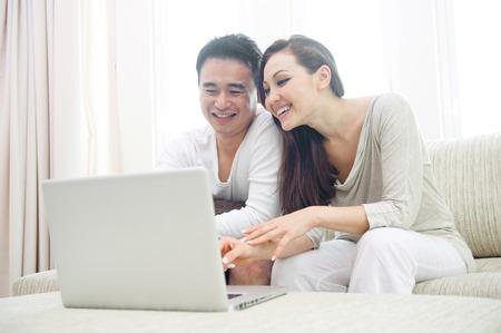 mujer descansando: Pareja asi�tica feliz usando la computadora port�til