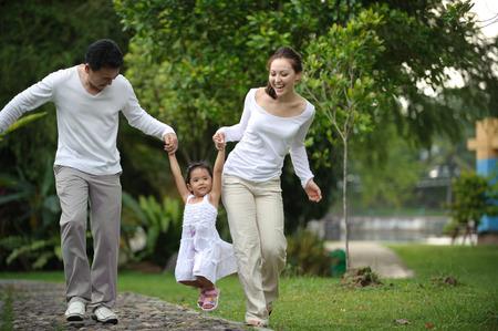 familias jovenes: Hija feliz de Asia caminando Familia en el parque