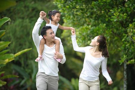 家族: 公園で家族との時間を一緒に楽しんで幸せなアジア家族