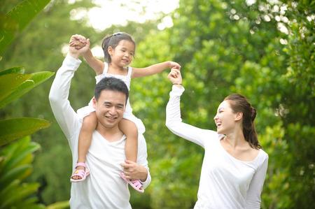 familias jovenes: Familia asi�tica feliz que disfruta de tiempo en familia en el parque