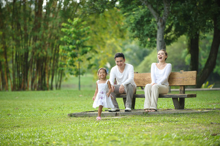 mother on bench: Happy Asian Family enjoying their time in the park