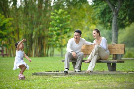 familia cenando: Familia asi�tica feliz disfrutando de su tiempo en el parque