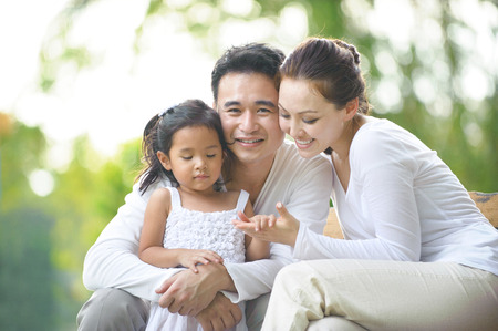 Happy Asian Family enjoying their time in the park photo