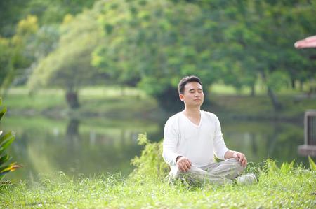 meditation man: Asian Man Meditating in the park Stock Photo