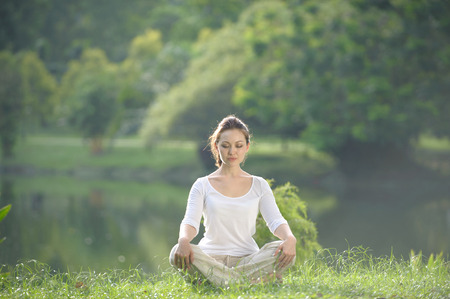 Attractive Healthy Asian Woman meditating in the park photo