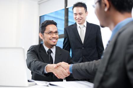 hand shake: Hombre de negocios asiático que sacude las manos