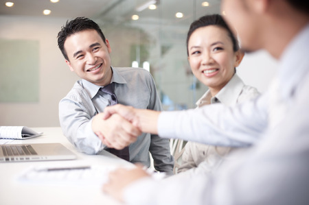 transaction: Asian Business Man smiling shaking hands