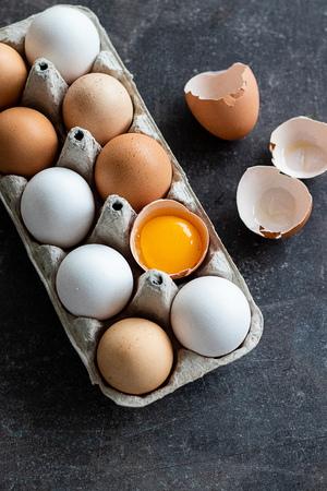 Uova crude organiche fresche, bianche, beige e marroni, una è incrinata Archivio Fotografico