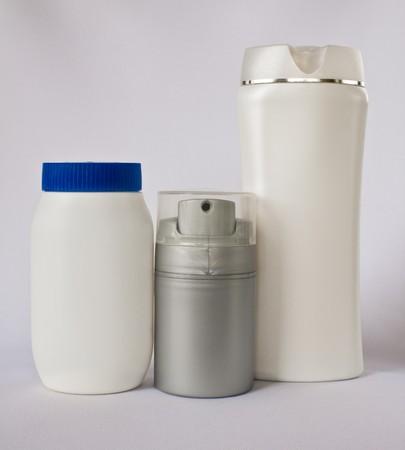 three blank bottle,shampoo, powder and moisturiser on white background photo