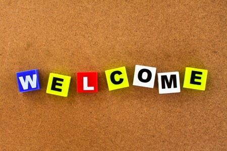 welcome sign: colorful letters with welcome isolated on wood board Stock Photo