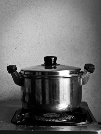 Crock on the gas stove over white background photo