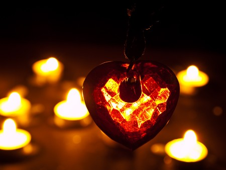 heart in crystal form under candle light photo