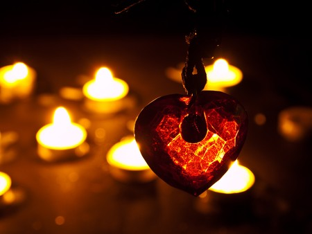 burning love: heart in crystal form under candle light Stock Photo