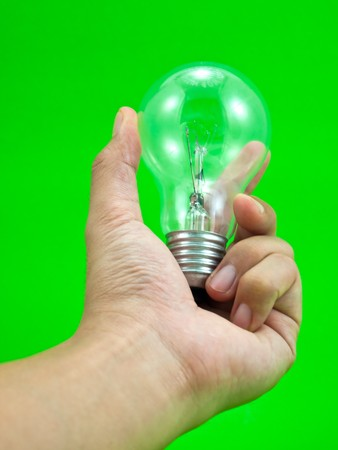 Lightbulb in a hand isolated on green background. Stock Photo - 8116286