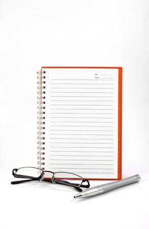 orange notebook (blank paper) and eyeglasses isolated on white background photo