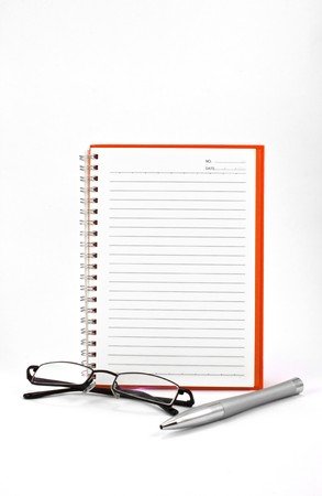 actuality: orange notebook (blank paper) and eyeglasses isolated on white background Stock Photo