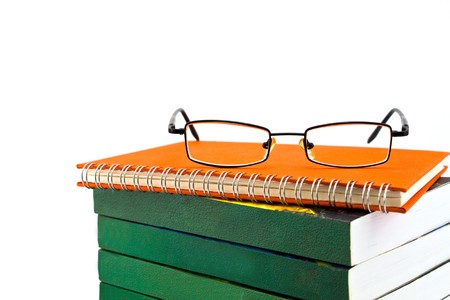Orange notebook and eyeglasses isolated on white background photo