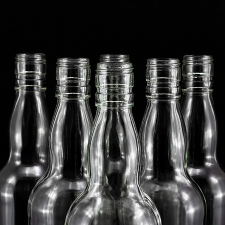 empty bottles collection, colorless, isolated on black backgrounde photo