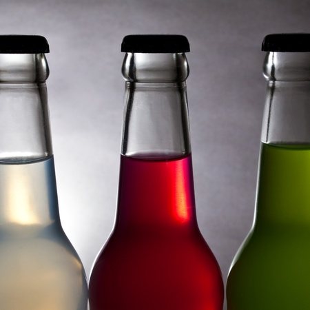 three colorful bottle of drink on light background photo