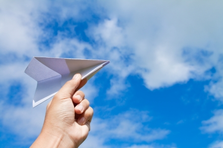 toy plane: hand with paper plane against blue sky