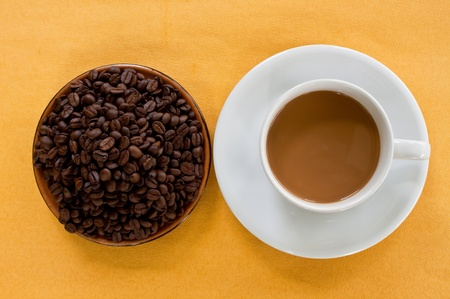 cup of coffee and coffee seed on plate photo