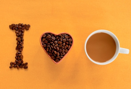 Heart shape made from coffee beans with a  cup of coffee, spelling I love coffee