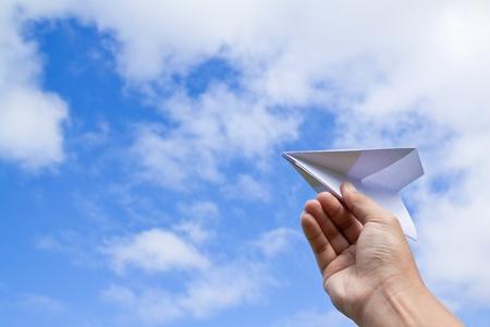papierflugzeug: Hand mit Papierflugzeug gegen blauen Himmel