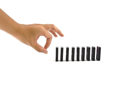 chain reaction: Hand ready to push domino pieces to cause chain reaction