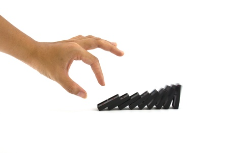 Hand to push domino pieces to cause chain reaction photo