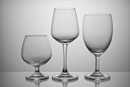 material de vidrio: Copa vac�a aislada sobre fondo gris Foto de archivo