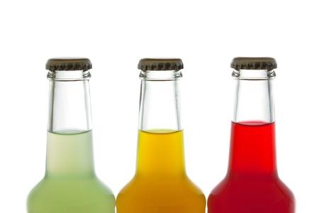 rainbow cocktail: tres botellas de bebida de colores sobre fondo blanco