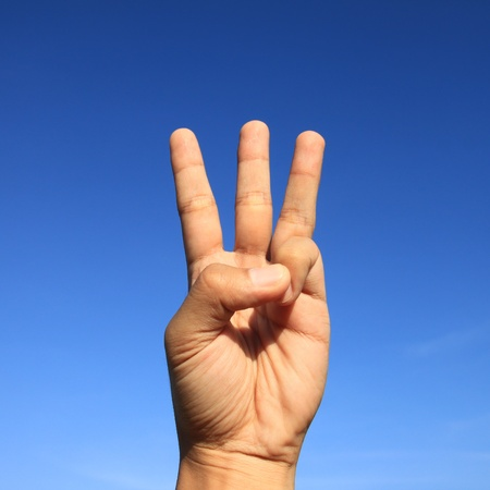 counting hand sign with blue sky photo