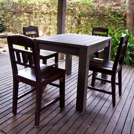 wooden chair and table between garden photo