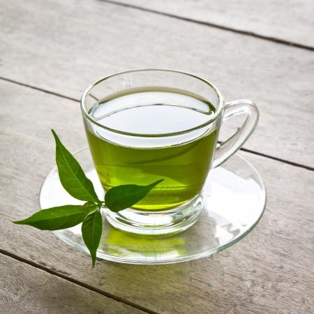 hojas de te: una taza de t� verde en el tablero de madera, beber a la salud Foto de archivo