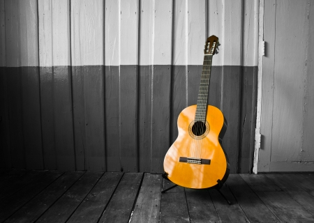 The guitar on the old wooden wall, color in black photo