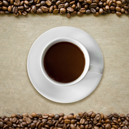 cup of coffee on wooden, surrounded with coffee beans photo